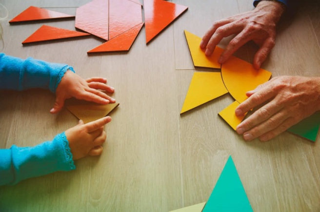 teacher and child playing with geometric shapes, learning concept